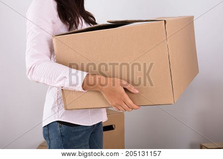 Close-up Of Woman Carrying Cardboard Box In House