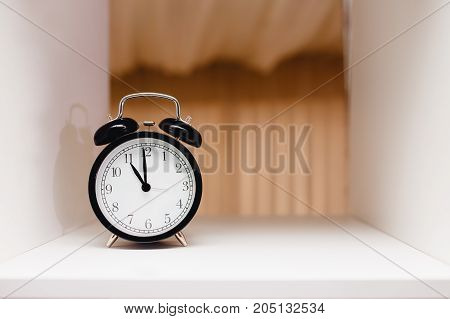 black alarm clock stands on a white shelf, space for text. copy space