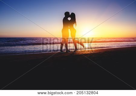 Silhouettes. Blur Couple kissing on beach with beautiful sunset in background