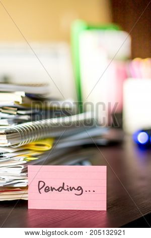 Pending; Stack Of Documents And Laptop At Working Desk.