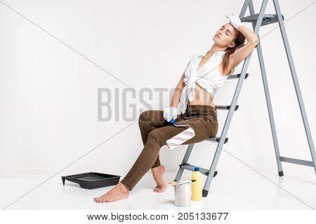 beautiful attractive woman resting after painting wall with paint roller in house