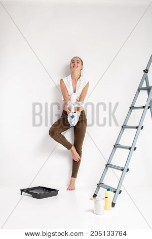 beautiful smiling woman painting wall with paint roller in house