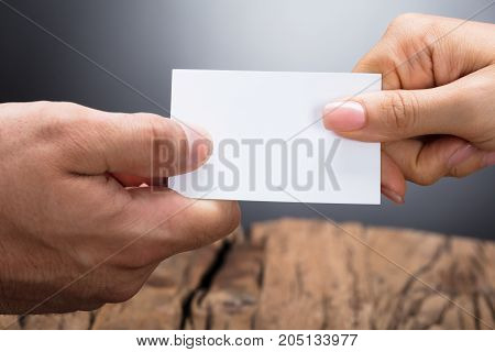 Close-up Of Two Businesspeople Hand Exchanging Blank White Visiting Card