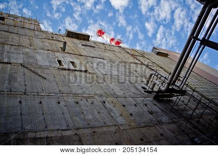 Concrete wall, pipes on blue sky background