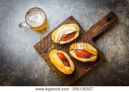 Choripan. Latin American Argentine and chilean food. Chorizo sausages hot dogs served with beer, top view.