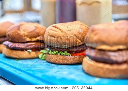 Three hamburgers. Only prigatovleny and lie in the workplace. On a blue board, close-up.