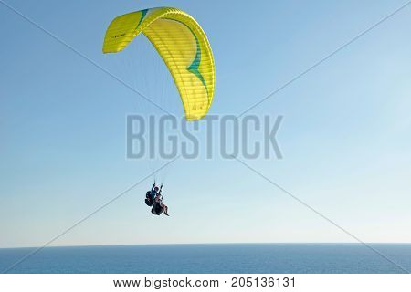 NETANYA, ISRAEL - AUGUST 29, 2015: Paraglider on Mediterranean sea coast, Netanya beach, Israel. Coast and quay of Netanya is popular place for paragliding