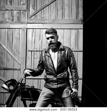 Handsome mature bearded biker man in leather jacket near motor bike with wine bottle in hands on wooden background square picture