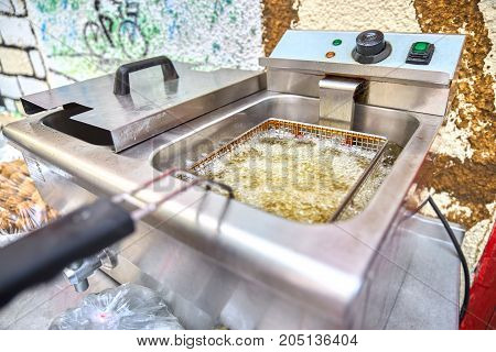 A deep pan industrial kitchen oil fryer, with golden oil, bubbling and frying potatoes, close-up