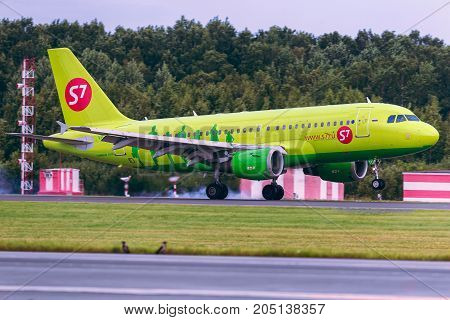 Pulkovo, Saint-Petersburg, Russia - August 10, 2017:   The airplane Airbus A319 of S7l Airlines is landing on the runway against the background of the forest and blue sky. Summer sunny weather