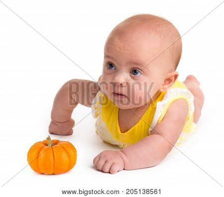 Baby girl with a small pumpkin isolated on a white background
