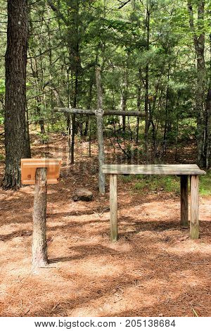 Wooden cross, lectern, and altar set in the woods for holding outdoor mass.
