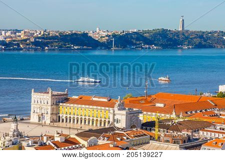 Lisbon aerial view from Sao Jorge Castle, Portugal, Europe. Close up of Cristo Rei in Almada, Tagus River and Comercio or Commerce Square with Rua Augusta Triumphal Arch on background. Urban skyline.