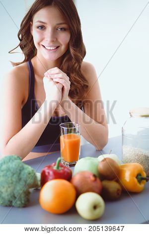 Girl sitting in kitchen on the desk with fruit and glasses with juice
