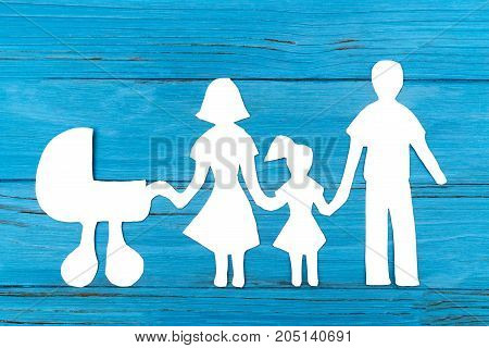 Paper silhouette of family with baby carriage on blue wooden background. Concept of family love