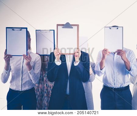 Team of businesspeople holding a folders near face isolated on white background . Businesspeople