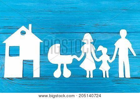 Paper silhouette of family with baby carriage, house on blue wooden background. Life insurance concept