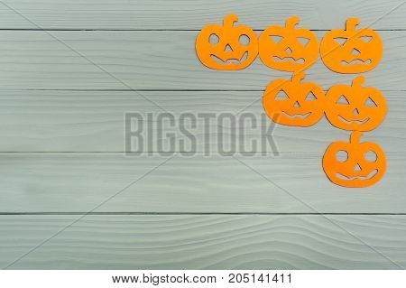 Corner frame on the right side with different pumpkin paper silhouettes on a gray wooden table. Halloween celebration. Copy space for greetings