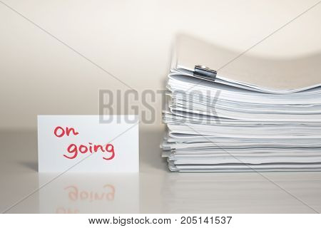On Going; Stack Of Documents On White Desk And Background.