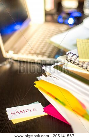 Sample; Stack Of Documents And Laptop At Working Desk.