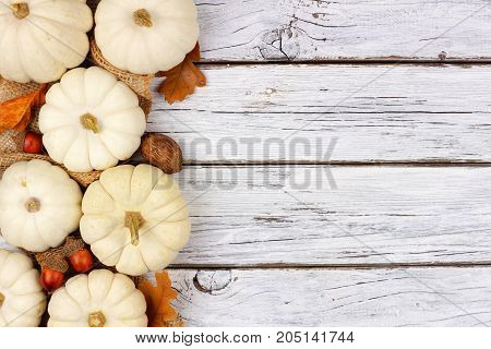 Autumn Side Border Of White Pumpkins And Brown Leaves Over A Rustic White Wood Background