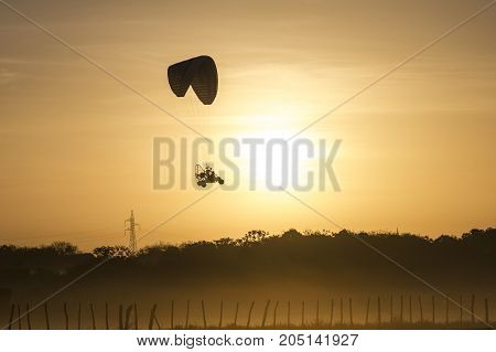 Powered paraglider flying at sunrise in foggy morning