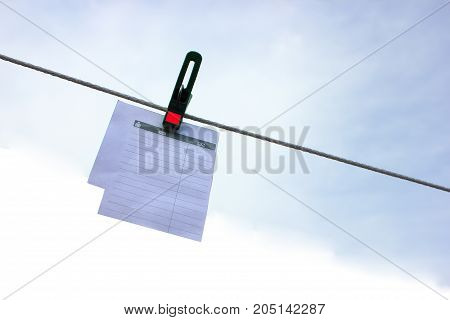 Paper sheet notepad hanging on a rope on clothespins on a light blue background. Space for text