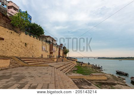 VARANASI INDIA - MARCH 13 2016: Wide angle picture of the yellow stairs and wall of Parakota Ghat in front of Ganges River in the city of Varanasi in India