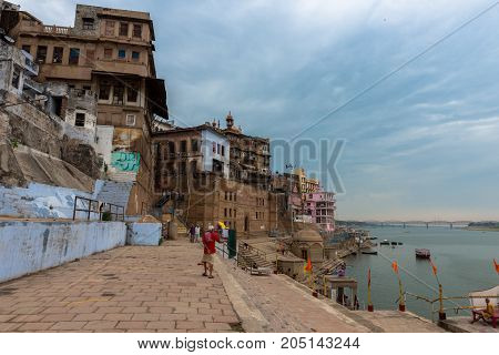 VARANASI INDIA - MARCH 13 2016: Wide angle picture of indian men walking in front of Ganges River in the city of Varanasi in India