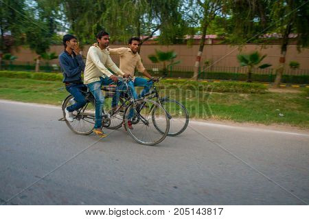 AGRA, INDIA - SEPTEMBER 19, 2017: Unidentified men rides a byke in the streets in central India in Agra, India.