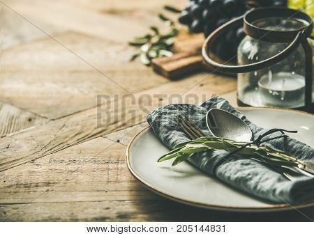 Fall holiday table party decoration setting. Plate with linen napkin, fork, spoon, candle holder, grapes on board, buns, olive tree branch over wooden background, selective focus, copy space