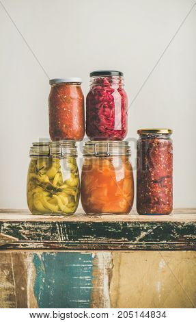 Autumn seasonal pickled or fermented colorful vegetables in jars over vintage kitchen drawer, white wall background, copy space. Vegetarian Fall home food preserving or canning concept