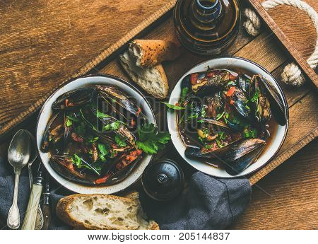Belgian boiled mussels in tomato sauce with fresh parsley in serving metal bowls and baguette bread slices and beer in bottle in wooden tray over rustic background, top view, copy space