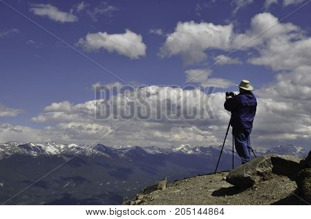Man with his camera on a tripod at the top of a ridge photographing the mountain range across from him.