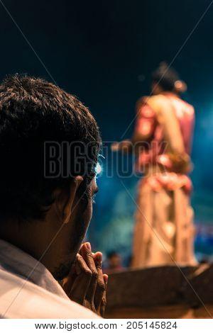 VARANASI INDIA - MARCH 13 2016: Vertical picture of unidentified Hindu indian man praying during Ganga Aarti ritual at Dashashwamedh Ghat in Varanasi India.