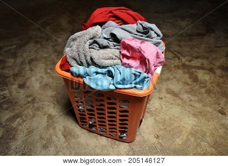 pile of colorful dirty cloth in orange basket on dirty cement ground for background