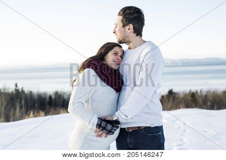A Pregnant couple have fun in winter nature