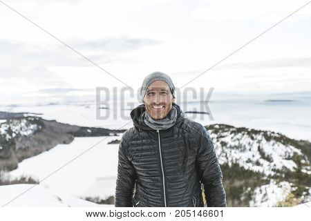 A Happy young man standing outdoors on winter mountain resort