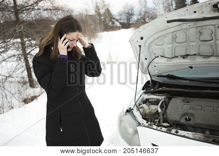 A girl on the winter road is calling the phone near the car