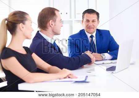 Business people sitting and discussing at meeting.