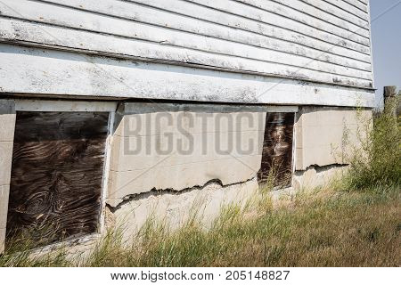 horizontal image of a crumbling cement foundation with windows boarded up along the foundation.