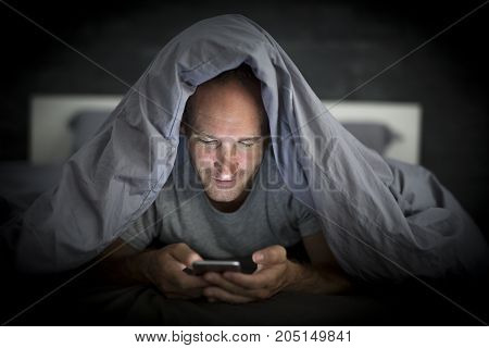 A young cell phone addict man awake late at night in bed using smartphone
