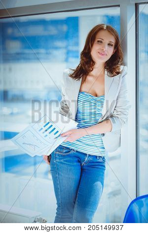 Happy businesswoman holding a paper standing in office.