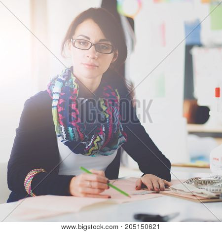 Beautiful fashion designer sitting at the desk in studio