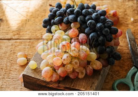 Two Type Of Fresh Ripe Grapes Blue And Green. On A Wooden Background. Close Up.
