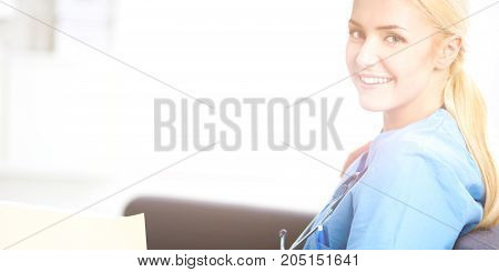 Closeup portrait of a happy young doctor sitting on the sofa with folder