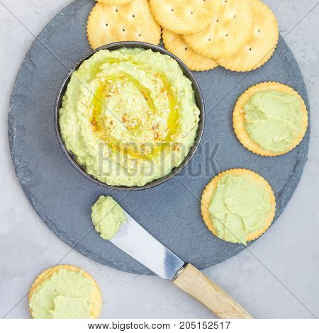 Avocado hummus sprinkled with olive oil paprika and sesame served with crackers top view square format