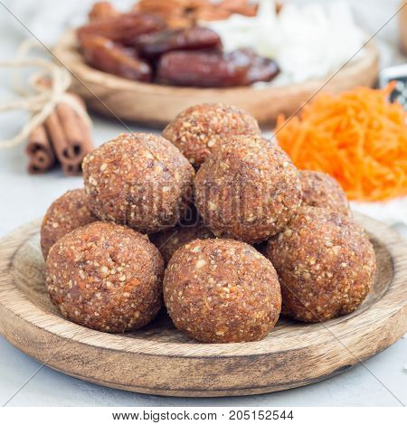 Healthy homemade paleo energy balls with carrot nuts dates and coconut flakes on a wooden plate square format