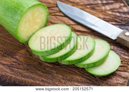 Preparing vegetable dish. Zucchini and zucchini slices on a wooden cutting board horizontal closeup