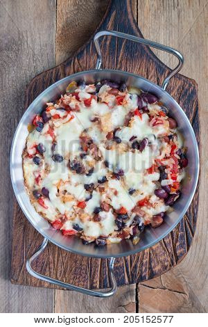 Baked rice casserole with different kinds of beans cheese and paprika in metal baking dish vertical top view